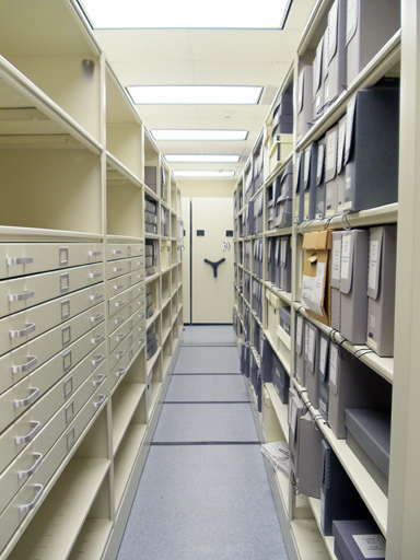 gray archival boxes on mobile shelving system